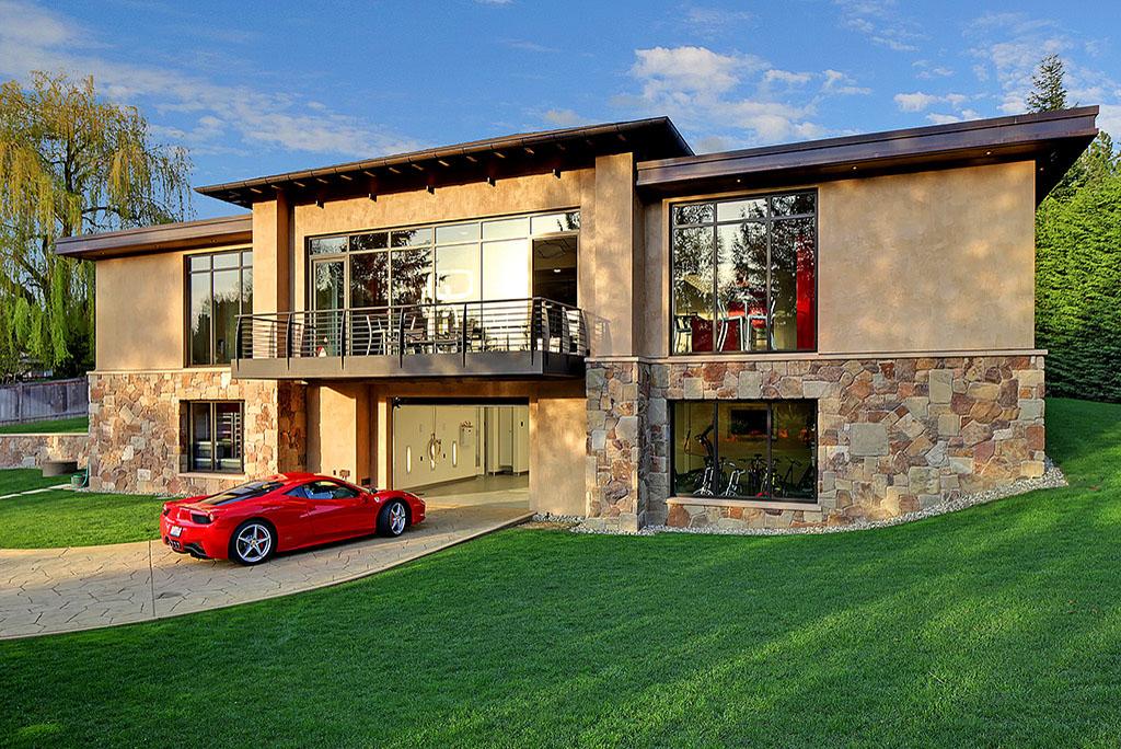 Casa de concreto con un carro estacionado de perfil