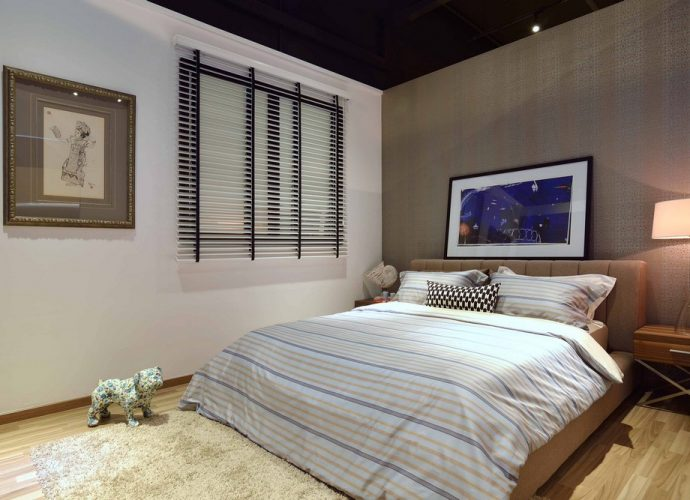 Una cama con edredón blanco y colores neutros como idea para renovar la recámara