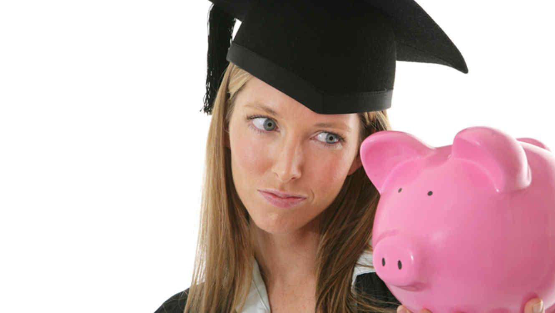 Mujer graduada sostiene un cerdito de alcancia